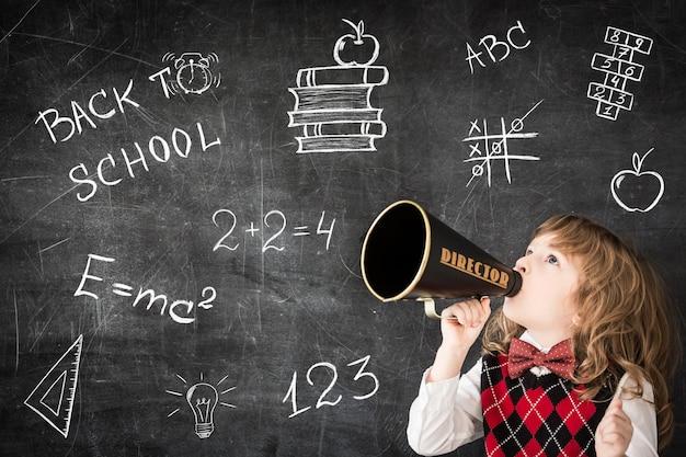 Умный ребенок кричит через мегафон в классе счастливый ребенок против доски концепция образования