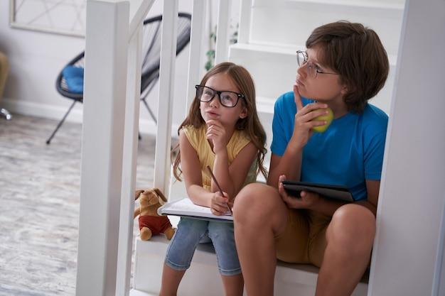 家の階段に座って宿題をしている賢い子供たちの思いやりのある弟と妹