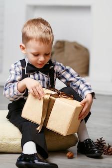 Умный маленький мальчик открывает подарок в елочных игрушках в ожидании чуда