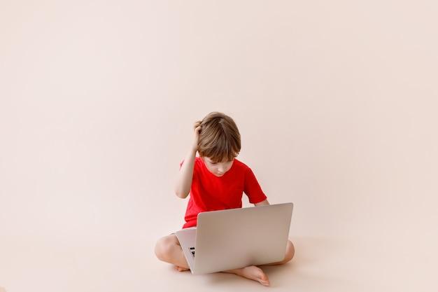 Умный маленький мальчик с ноутбуком в повседневной одежде. концепция технологии онлайн-обучения.