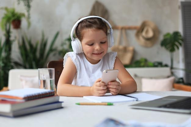 헤드폰을 끼고 있는 똑똑한 소녀는 스마트폰으로 온라인 숙제를 하고, 이어폰을 끼고 인터넷에서 공부하고, 검역 중에 웹 회의나 수업을 합니다.