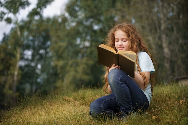 Smart little girl reading the book outdoors.