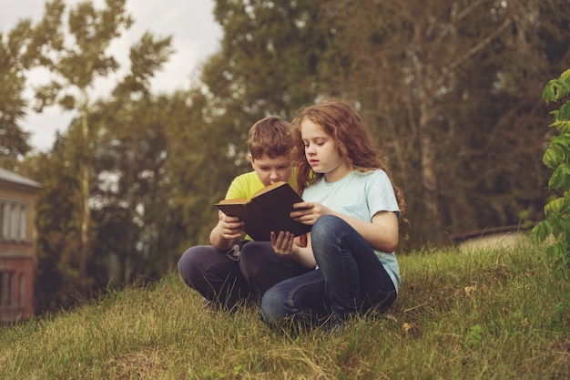Smart little kids reading the book outdoors.