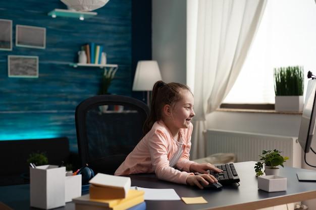 Умный маленький ученик, глядя на экран монитора компьютера