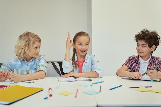 Умная маленькая школьница, глядя в сторону, подняла руку во время учебы, сидя за столом в