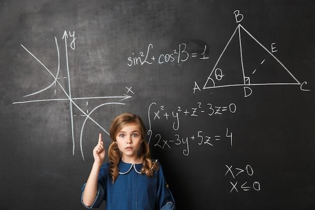 Smart little schoolgirl standing at the blackboard with math graphics written on it