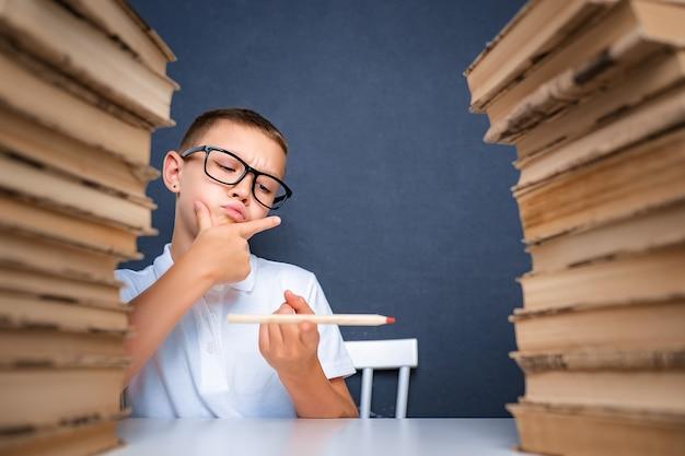 그의 손에 연필을 들고 멀리보고 생각하고 스마트 찾고 소년. 집중적으로 문제를 연구하고 연구하고 해결합니다.