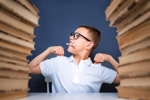 그의 입에 연필을 들고 멀리보고 생각하고 스마트 찾고 소년. 집중적으로 문제를 연구하고 연구하고 해결합니다.