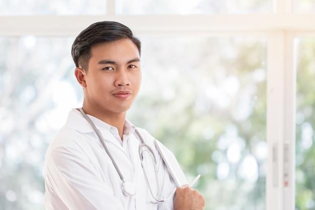 病院や診療所で患者を治療する情報を検索するための聴診器を首に装着した白いガウンスイートを備えたタブレットコンピューター探しカメラを保持しているスマートな男性医師、ヘルスケア医療コンセプト