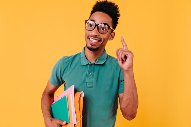 本でポーズをとる茶色の肌を持つスマートな男性モデル。トレンディなメガネをかけて楽しんでいる至福の留学生の屋内ポートレート。