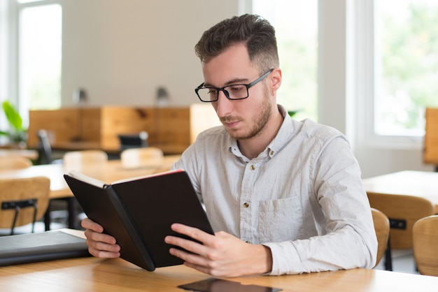 Smart male student reading textbook at desk in classroom
