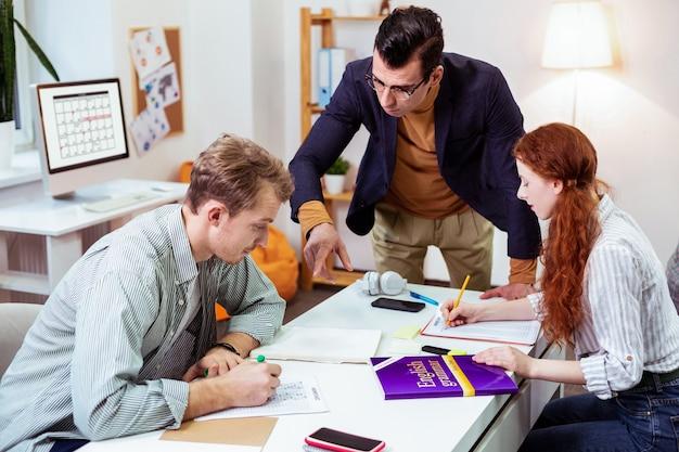 평가 시험을 도와주는 동안 학생 근처에 서있는 똑똑한 남자 교사
