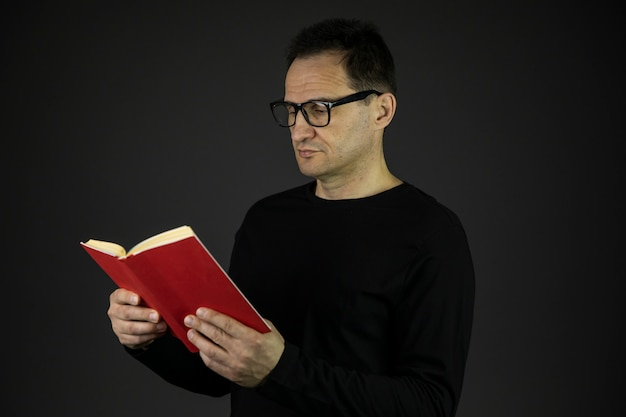 Smart man in casual black wear and glasses relaxing reading interesting book