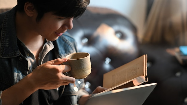 A smart man is drinking a coffee while reading a book and sitting at the black leather sofa