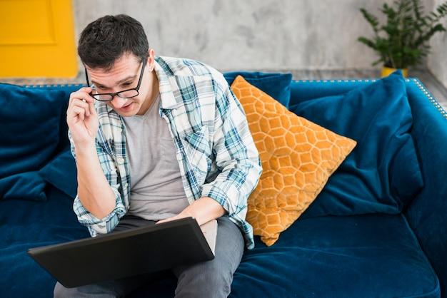 スマートな男がソファーに座っているとラップトップを見て