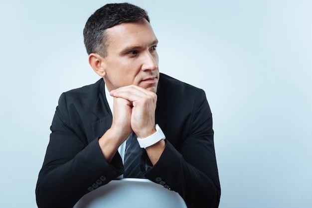 賢い人。椅子に座って、彼の仕事について考えながら脇を見ている思いやりのある素敵なハンサムなビジネスマン