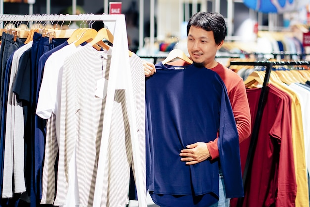 Smart man with beard try clothes in clothing store at shopping center