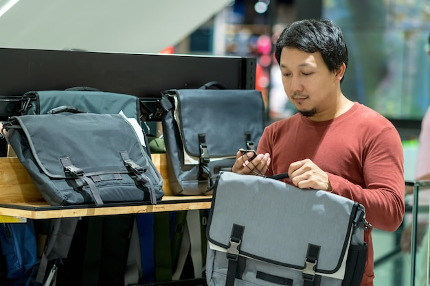 Smart man with beard trying bag and checking the price for make decision