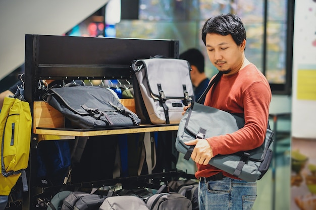 Smart man with beard trying bag and making decision in fashion bags shop at shopping mall