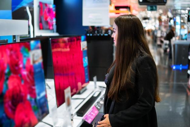 Умная современная покупательница выбирает большие телевизоры в магазине электроники. новые поколения экранов.