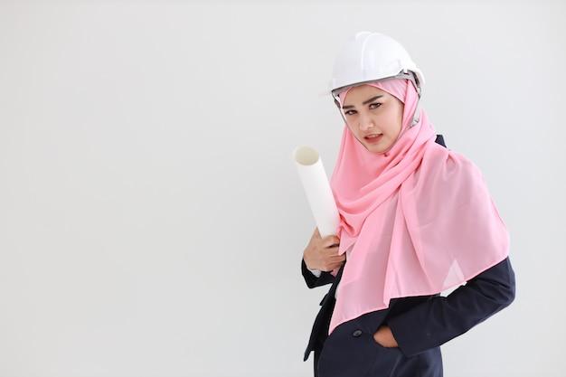 Умная мусульманская молодая азиатская женщина в синем костюме улыбается уверенно, держа план в студии