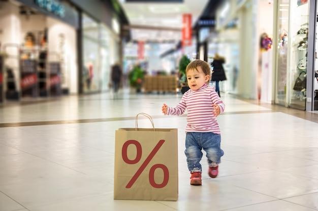 Умная природа дружелюбная черная пятница распродажа концепция покупок. крупным планом маленькая милая девочка бежит к экологически чистому бумажному пакету для покупок в торговом центре со знаком%. мягкий фокус, размытие фона