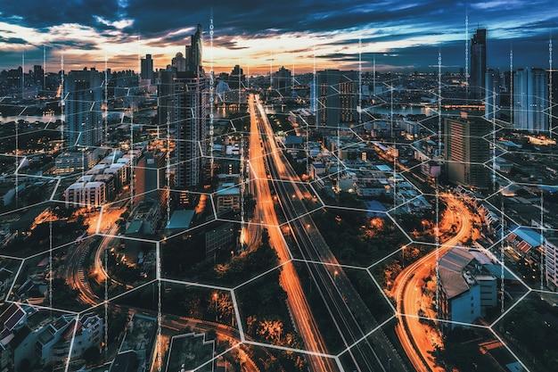 Концепция интеллектуальной сети и технологии подключения на фоне города бангкок ночью в таиланде, панорамный вид