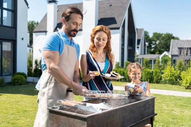 彼の家族と一緒に時間を過ごしながらバーベキューを準備するスマートなナイスマン