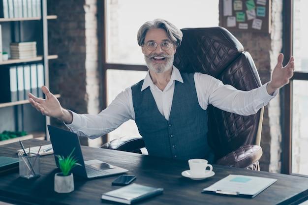 Умный старый бизнесмен сидит за столом, приглашает в офис