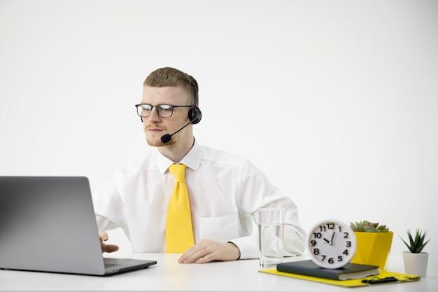 ヘッドセットを備えたスマートなオンラインコンサルタントが、ミニマルなオフィスのコールセンターで働いています。
