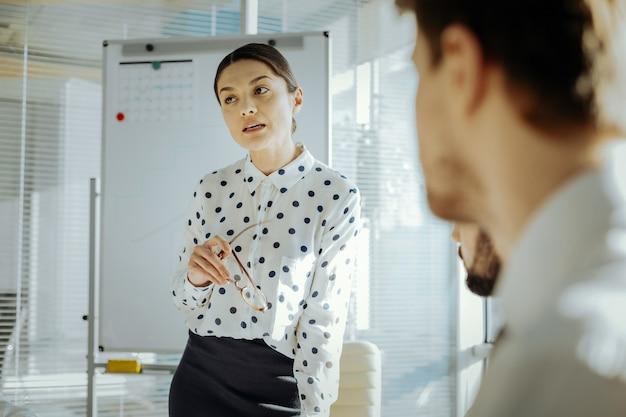 賢い意見。会議中に立ち上がって、重要な仕事関連の問題についての彼女の見解を表現しているかなり若い女性