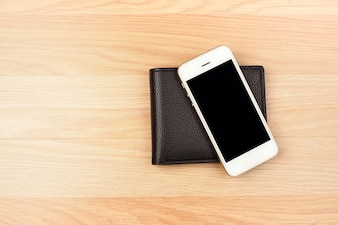 Smart phone and black wallet on wooden floor background. top view