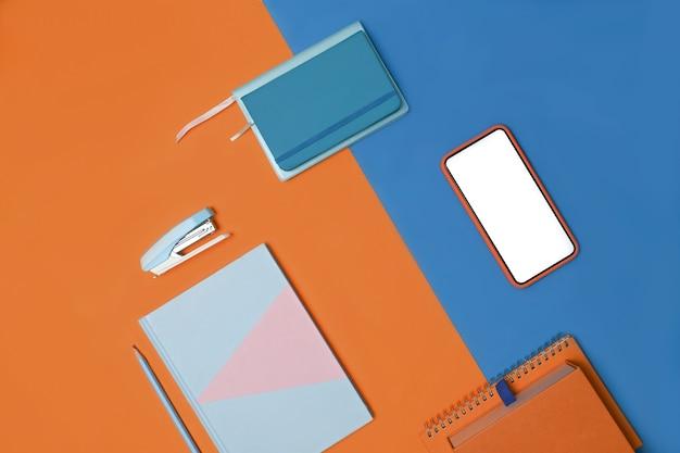 2トーンの青とオレンジの背景にスマートフォンとノートブック。