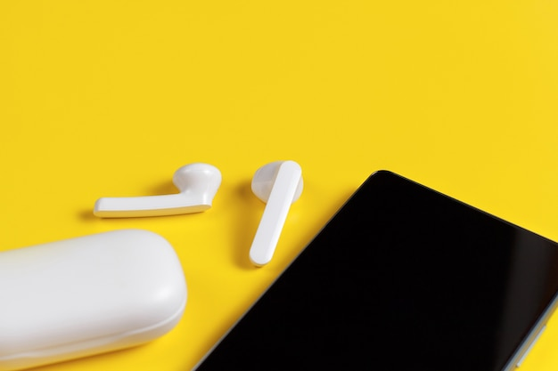 노란색에 케이스 평면도가있는 스마트 폰 및 흰색 무선 이어폰