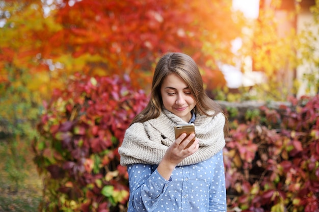 Smart phone autumn woman writting sms on mobile phone in fall