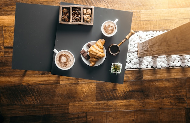 Smart phone and black fried coffee beans in cafe with cookie and cake on dark textured background