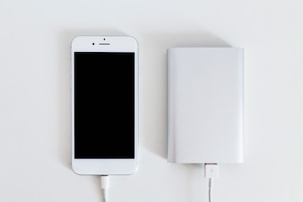 Smart phone connected with power bank charger over the white background