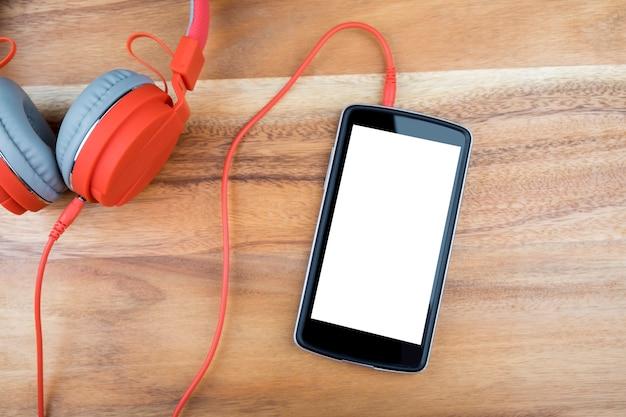 나무 책상에 빈 흰색 화면이 스마트 폰 장치.