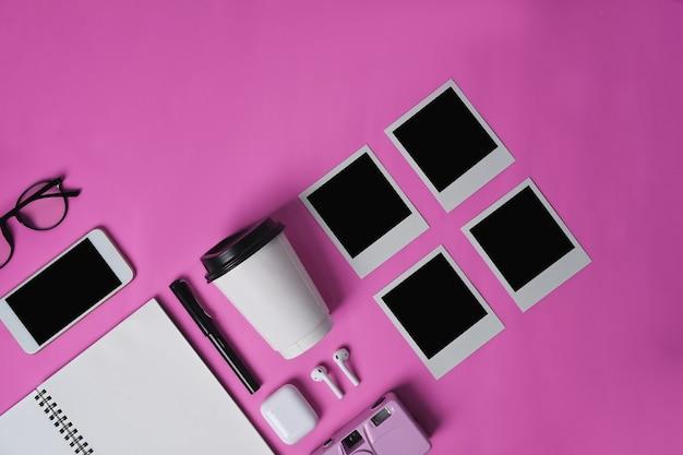 Смартфон, наушники, ноутбук, чашка и пустая рамка для фотографий на розовом фоне.