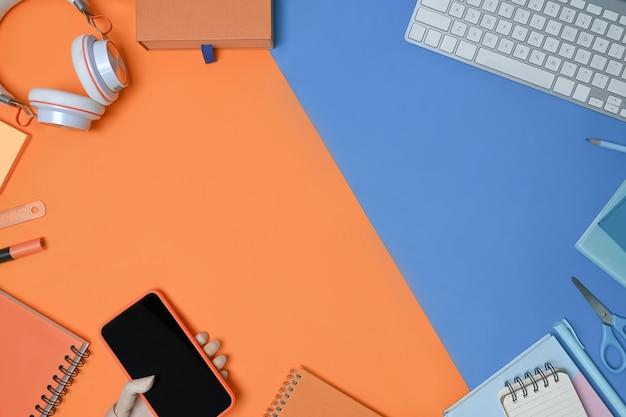 青とオレンジの2トーンの背景にスマートフォン、ヘッドフォン、キーボード、ノートブック。