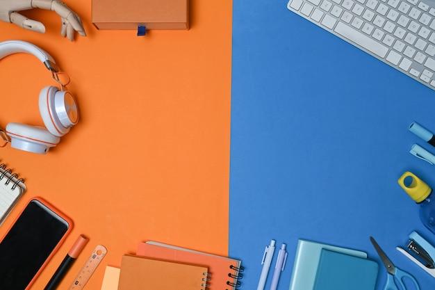 青とオレンジの2トーンの背景にスマートフォン、ヘッドフォン、文房具、ノートブック。