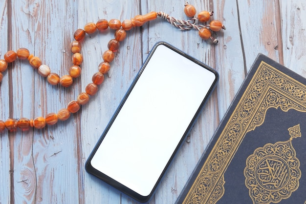 Smart phone, holy book quran and rosary on table,