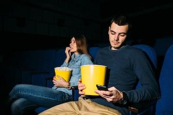 映画館のスマートフォン。映画館で映画を見ながらスマートフォンを使っている男。