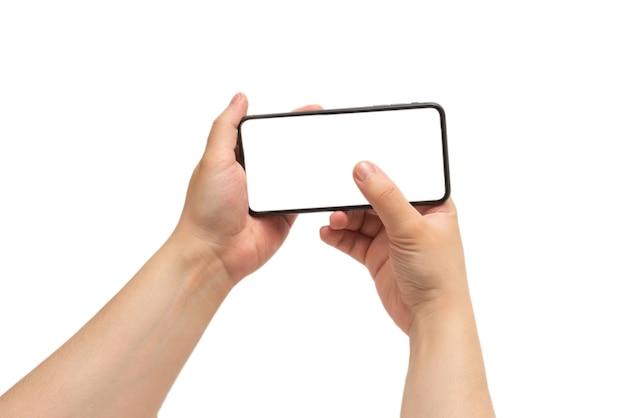 白い背景で隔離の男の手でスマートフォン。白い画面。コピースペース。