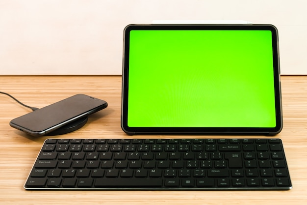 Smart phone is charging on wireless charging next to the tablet and keyboard