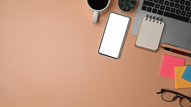 Smart phone, laptop computer, sticky notes and coffee cup on beige background.