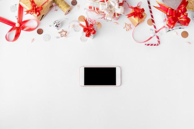 クリスマスの時間にモックアップのための孤立した白い画面のテーブルにスマートフォンのモバイルディスプレイ