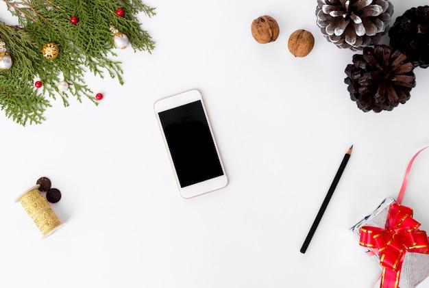 モックアップのための孤立した白い画面を備えたテーブル上のスマートフォンのモバイルディスプレイ