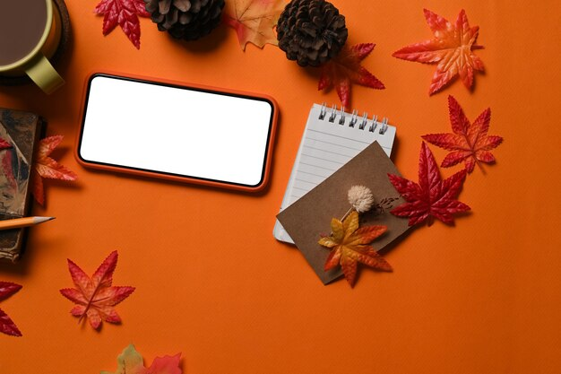 스마트 폰, 노트북, 커피 컵, 솔방울, 가을 단풍나무 잎은 주황색 배경에 있습니다.
