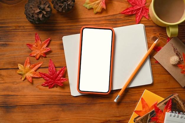 스마트 폰, 노트북, 커피 컵, 소나무 콘, 가을 단풍나무 잎이 나무 테이블에 있습니다.